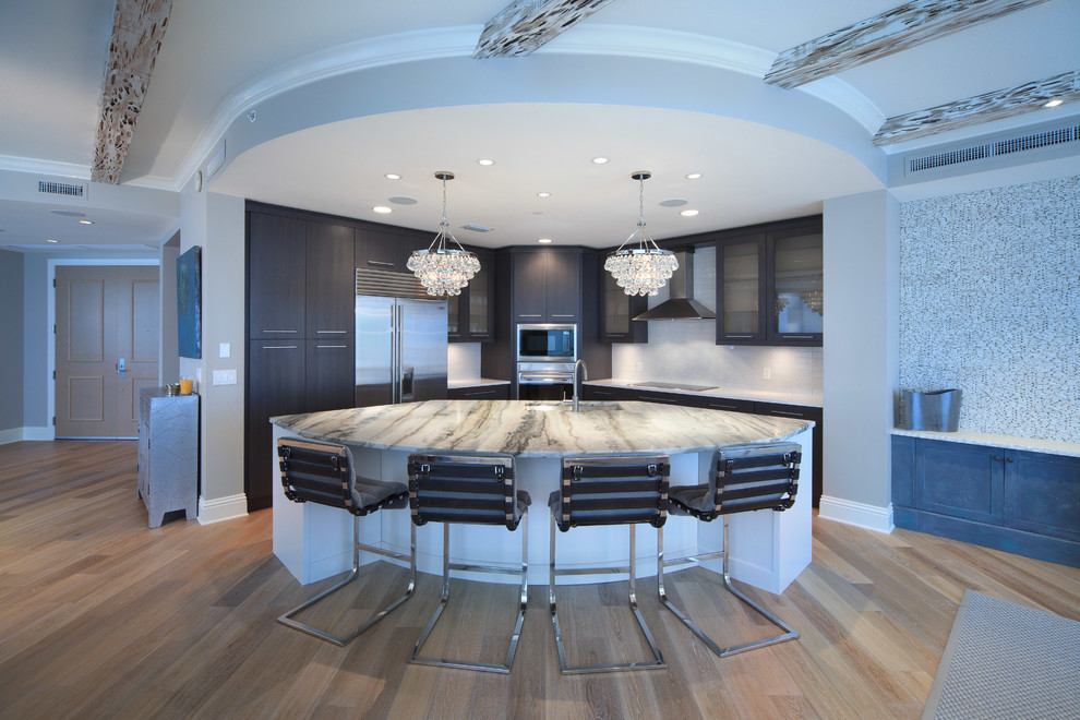 Example of a trendy l-shaped open concept kitchen design in Tampa with flat-panel cabinets, dark wood cabinets, white backsplash and stainless steel appliances