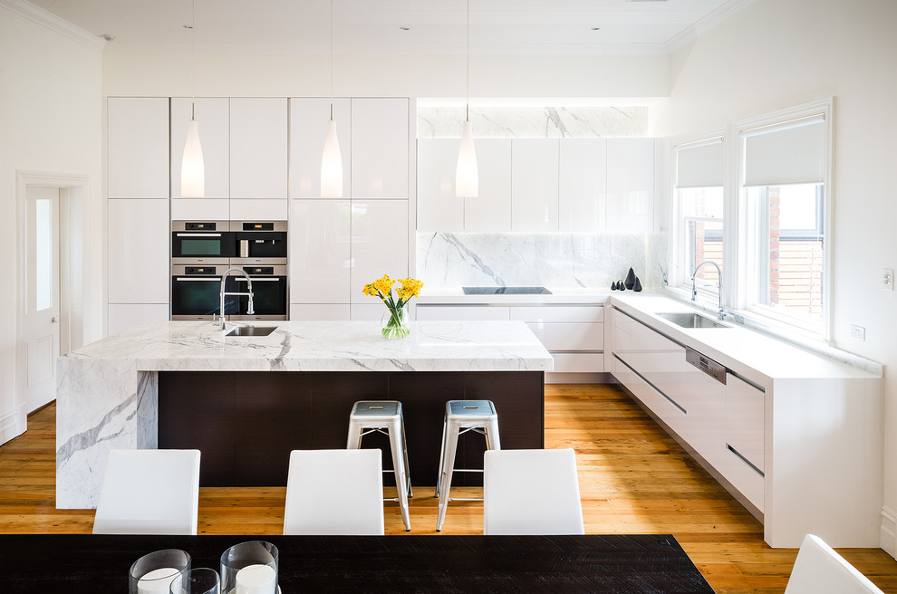 Example of a huge trendy l-shaped medium tone wood floor eat-in kitchen design in Melbourne with an undermount sink, flat-panel cabinets, white cabinets, marble countertops, an island, white backsplash, stainless steel appliances and marble backsplash