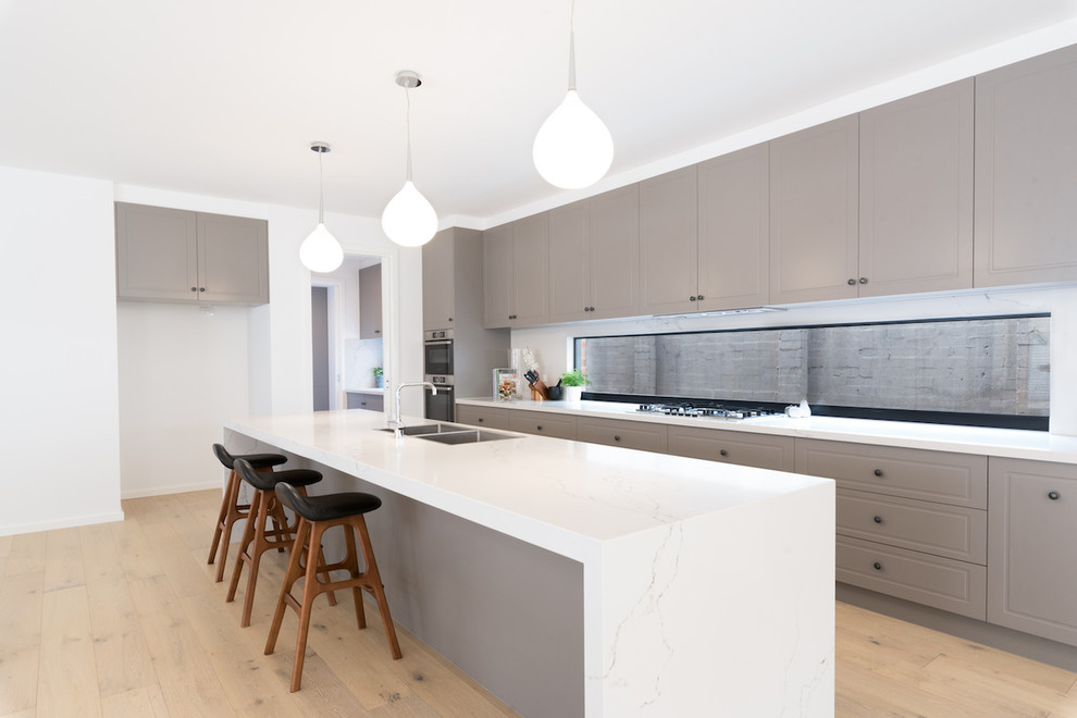 This is an example of a large contemporary galley open plan kitchen in Melbourne with a double-bowl sink, white splashback, stainless steel appliances, light hardwood floors, an island and white benchtop.