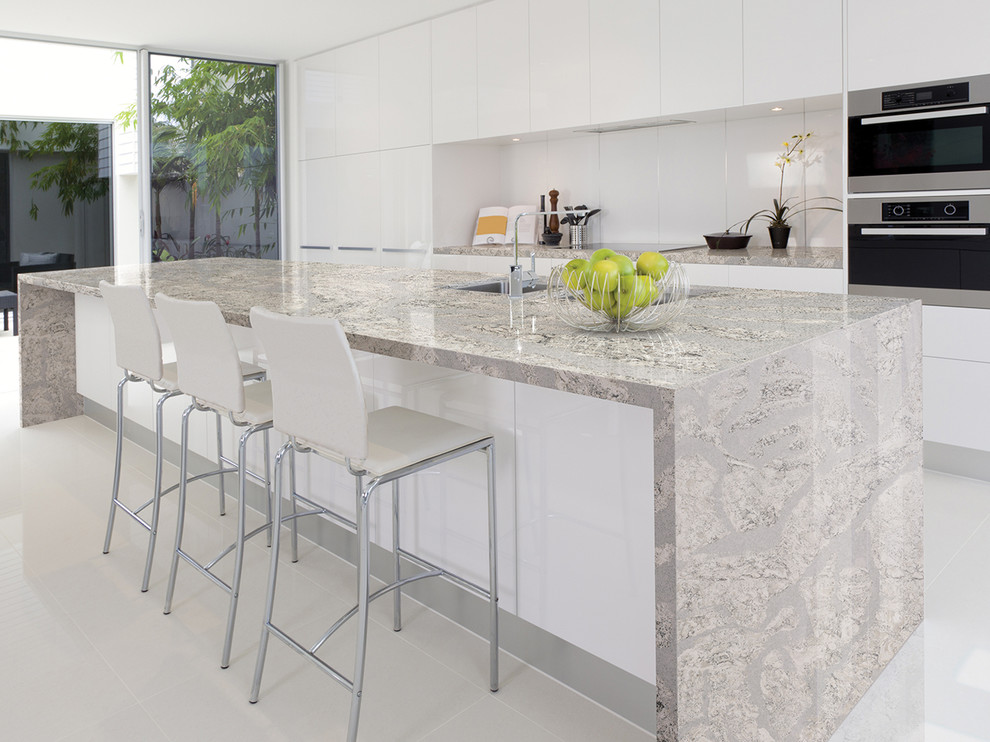 Inspiration for a mid-sized modern galley open concept kitchen remodel in San Diego with flat-panel cabinets, white cabinets, quartz countertops, white backsplash, white appliances and an island