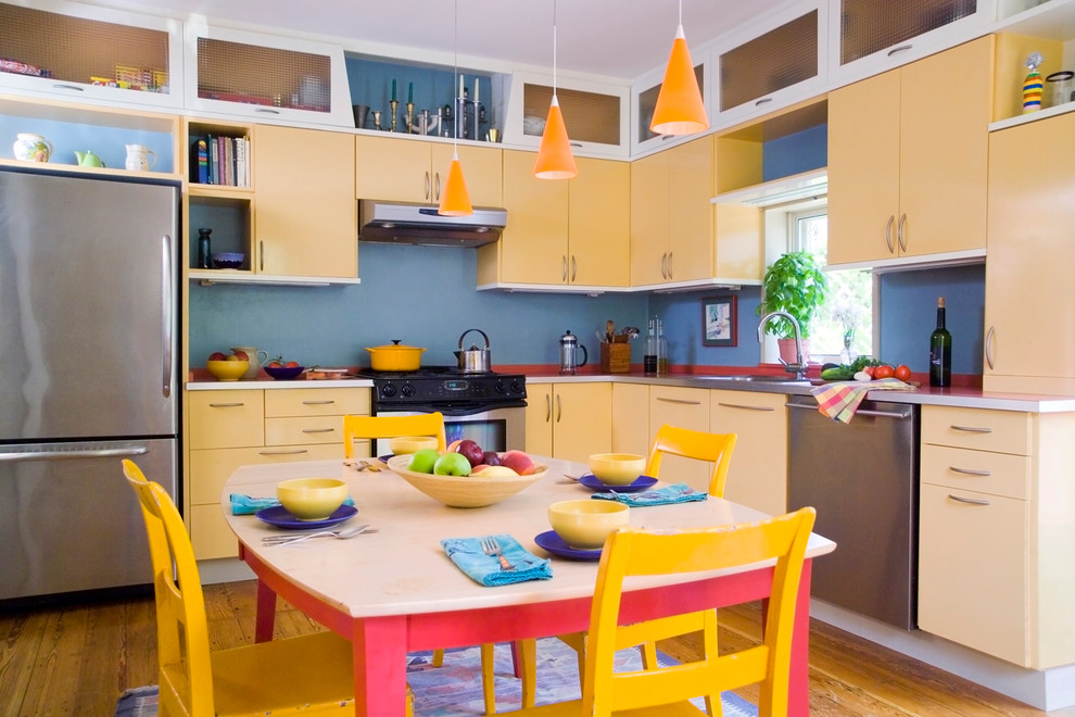 Mid-sized eclectic l-shaped medium tone wood floor eat-in kitchen photo in Boston with stainless steel appliances, yellow cabinets, an undermount sink, flat-panel cabinets, solid surface countertops and no island