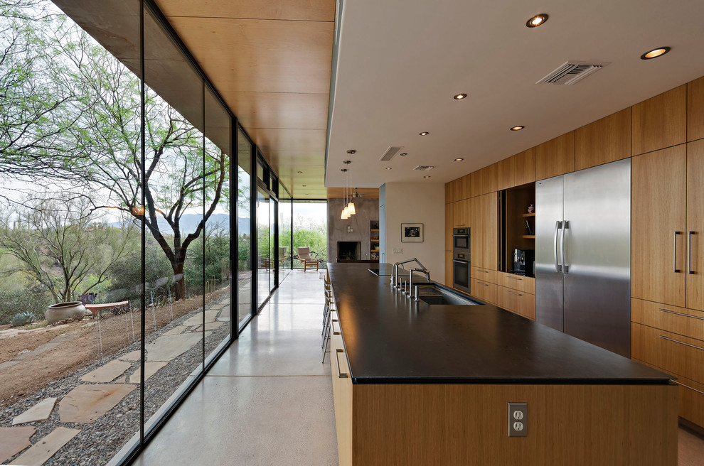 Kitchen - large modern galley concrete floor kitchen idea in Phoenix with an undermount sink, flat-panel cabinets, medium tone wood cabinets and stainless steel appliances