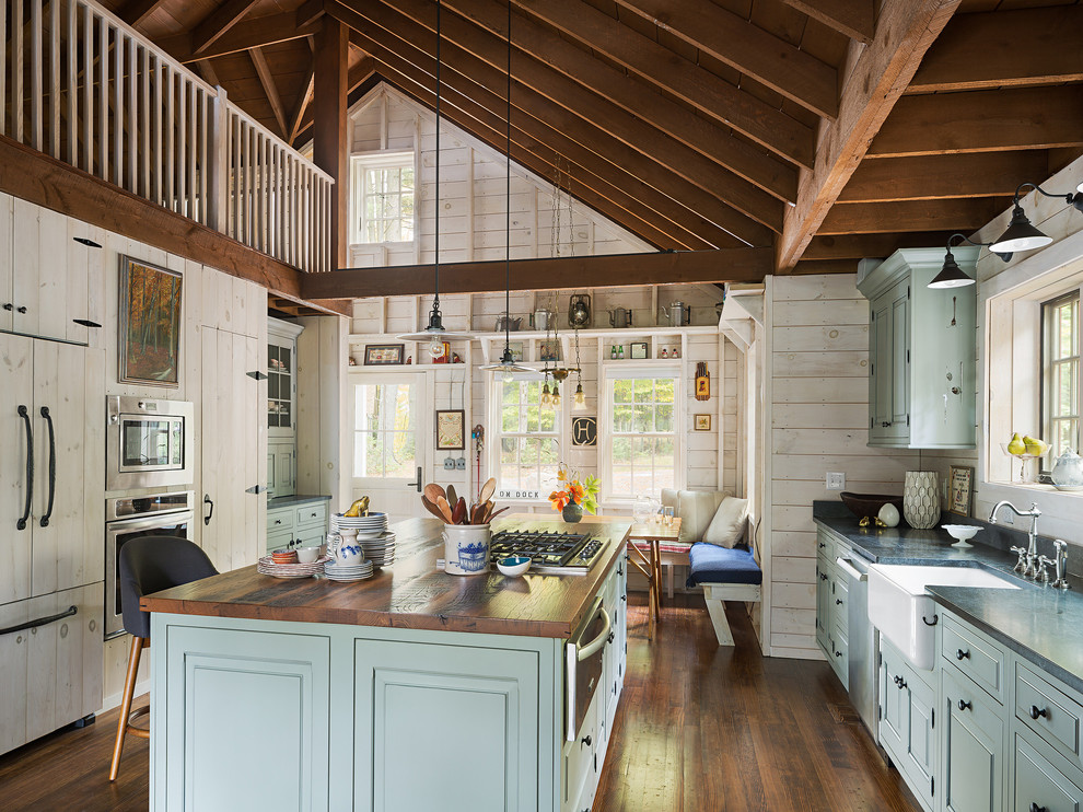 Example of a large mountain style dark wood floor eat-in kitchen design in New York with a farmhouse sink, raised-panel cabinets, blue cabinets, granite countertops, stainless steel appliances and an island