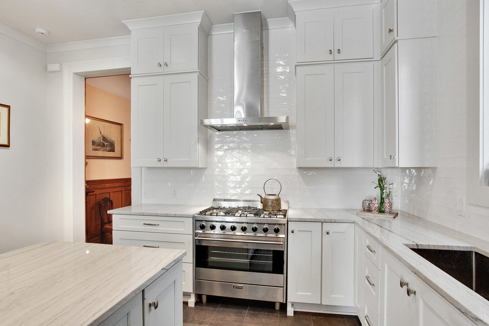 Inspiration for a large transitional l-shaped ceramic tile and brown floor kitchen remodel in New Orleans with an undermount sink, shaker cabinets, white cabinets, quartzite countertops, white backsplash, subway tile backsplash, stainless steel appliances, an island and white countertops