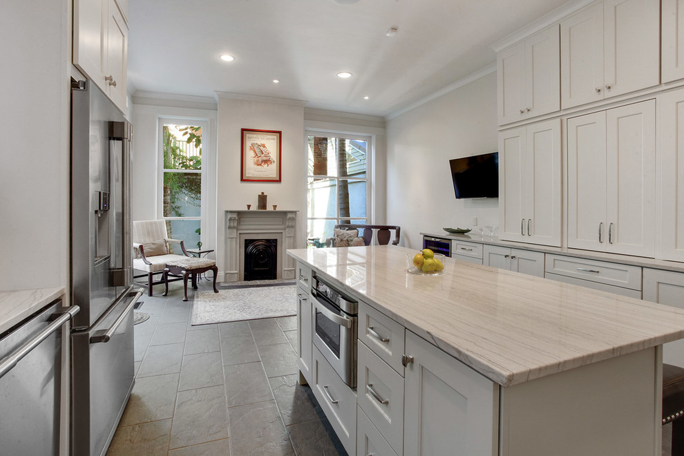 Inspiration for a large transitional l-shaped ceramic tile and brown floor kitchen remodel in New Orleans with white cabinets, quartzite countertops, stainless steel appliances, an island, an undermount sink, shaker cabinets, white backsplash, subway tile backsplash and white countertops