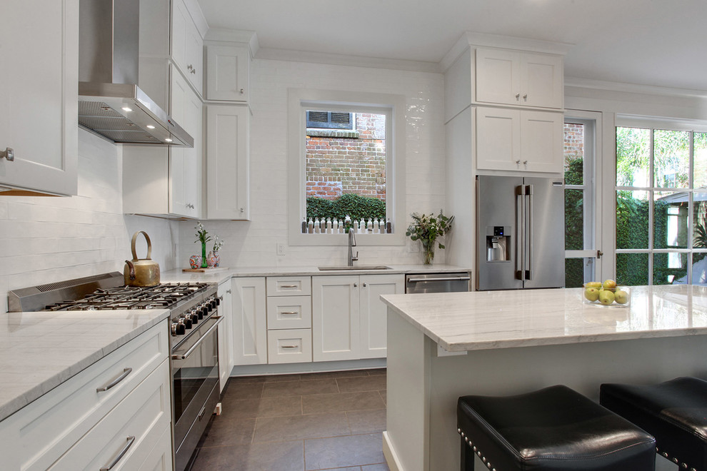 Kitchen - large transitional l-shaped ceramic tile and brown floor kitchen idea in New Orleans with an undermount sink, shaker cabinets, white cabinets, quartzite countertops, white backsplash, subway tile backsplash, stainless steel appliances, an island and white countertops