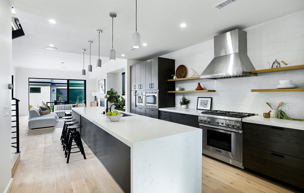 Example of a huge trendy galley light wood floor and beige floor kitchen design in Los Angeles with flat-panel cabinets, quartz countertops, white backsplash, porcelain backsplash, stainless steel appliances, an island, white countertops, an undermount sink and black cabinets