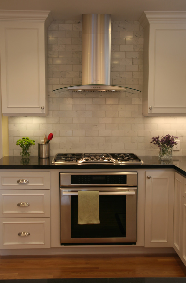 Example of a classic kitchen design in San Francisco with stainless steel appliances, recessed-panel cabinets, white cabinets, stone tile backsplash and gray backsplash