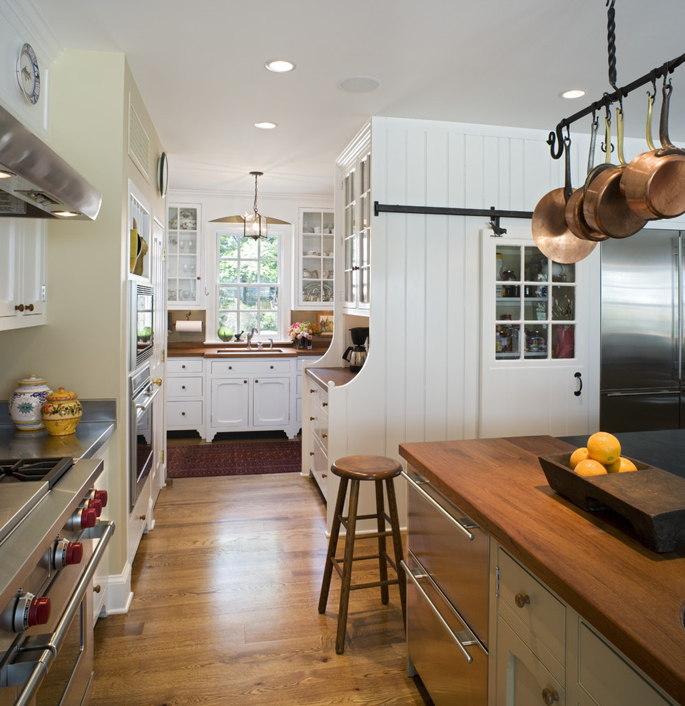 Kitchen - large traditional medium tone wood floor kitchen idea in Philadelphia with stainless steel appliances, wood countertops, an undermount sink, white cabinets and an island