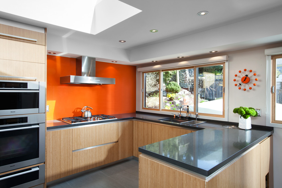 Mid-sized 1960s u-shaped ceramic tile and gray floor eat-in kitchen photo in Vancouver with flat-panel cabinets, light wood cabinets, concrete countertops, orange backsplash, glass sheet backsplash, stainless steel appliances, an undermount sink and a peninsula