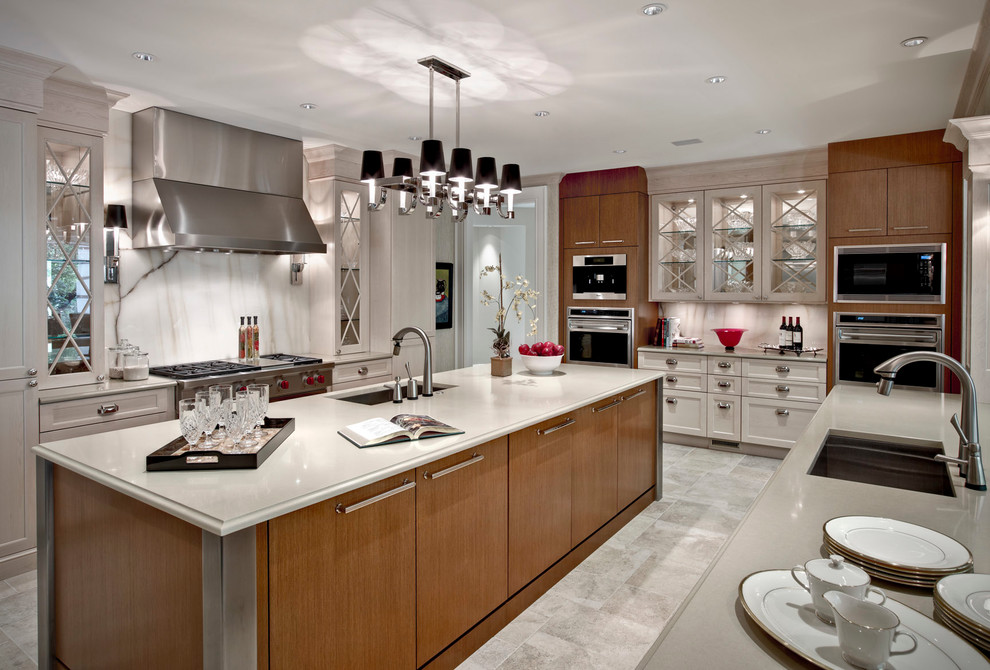 Transitional eat-in kitchen photo in Detroit with an undermount sink, recessed-panel cabinets, white backsplash, stainless steel appliances, stone slab backsplash and medium tone wood cabinets