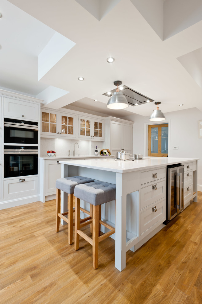 Inspiration for a mid-sized transitional galley light wood floor and beige floor kitchen remodel in Kent with shaker cabinets, white cabinets, black appliances, an island and white countertops