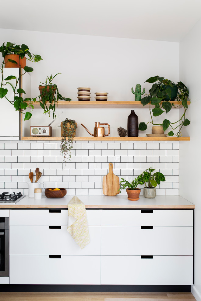 Design ideas for a mid-sized scandinavian kitchen in Melbourne with flat-panel cabinets, white cabinets, white splashback, subway tile splashback and light hardwood floors.