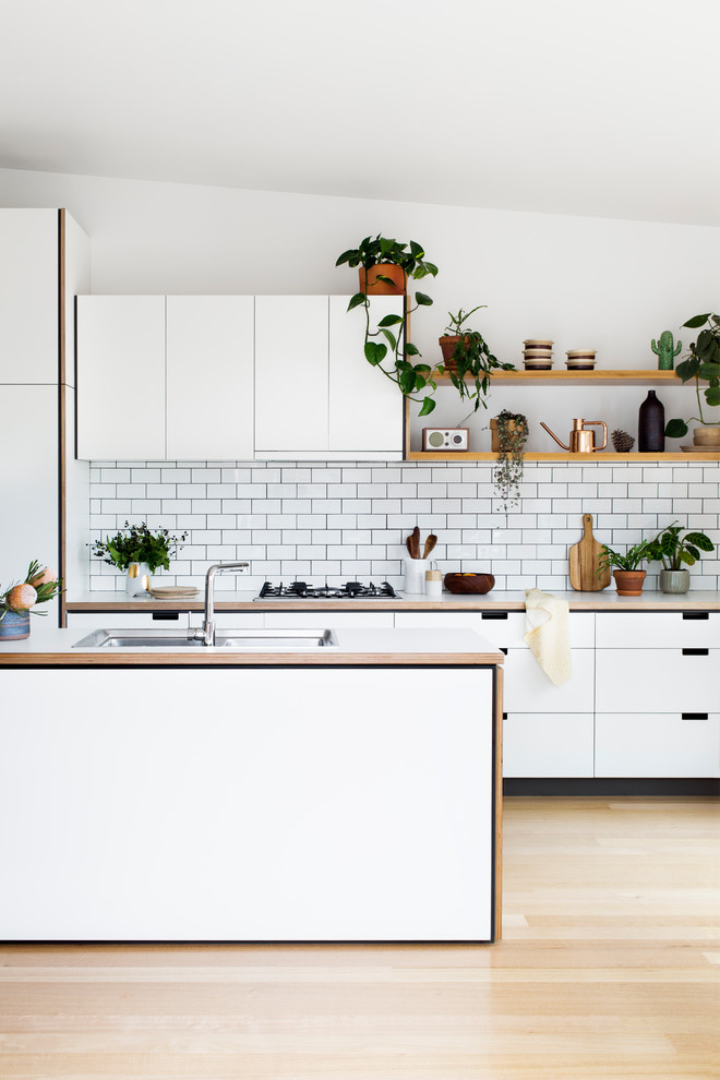 Trendy light wood floor kitchen photo in Melbourne with a double-bowl sink, flat-panel cabinets, white cabinets, white backsplash and subway tile backsplash
