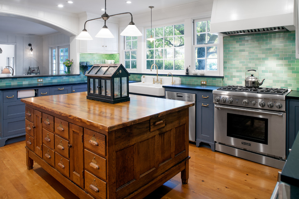 Eat-in kitchen - mid-sized farmhouse u-shaped medium tone wood floor eat-in kitchen idea in Los Angeles with a farmhouse sink, shaker cabinets, gray cabinets, green backsplash, ceramic backsplash, stainless steel appliances, an island and wood countertops