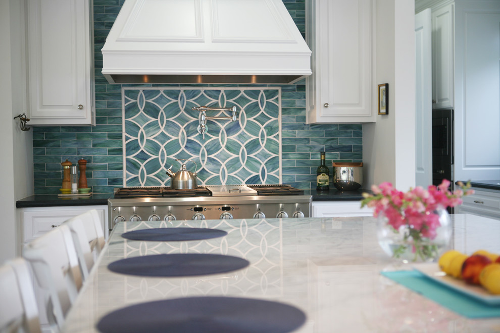 Inspiration for a large timeless l-shaped medium tone wood floor open concept kitchen remodel in Los Angeles with raised-panel cabinets, white cabinets, blue backsplash, stainless steel appliances, a farmhouse sink, quartz countertops, porcelain backsplash and an island