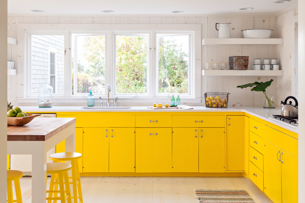 Example of a beach style l-shaped kitchen design in Boston with flat-panel cabinets and yellow cabinets