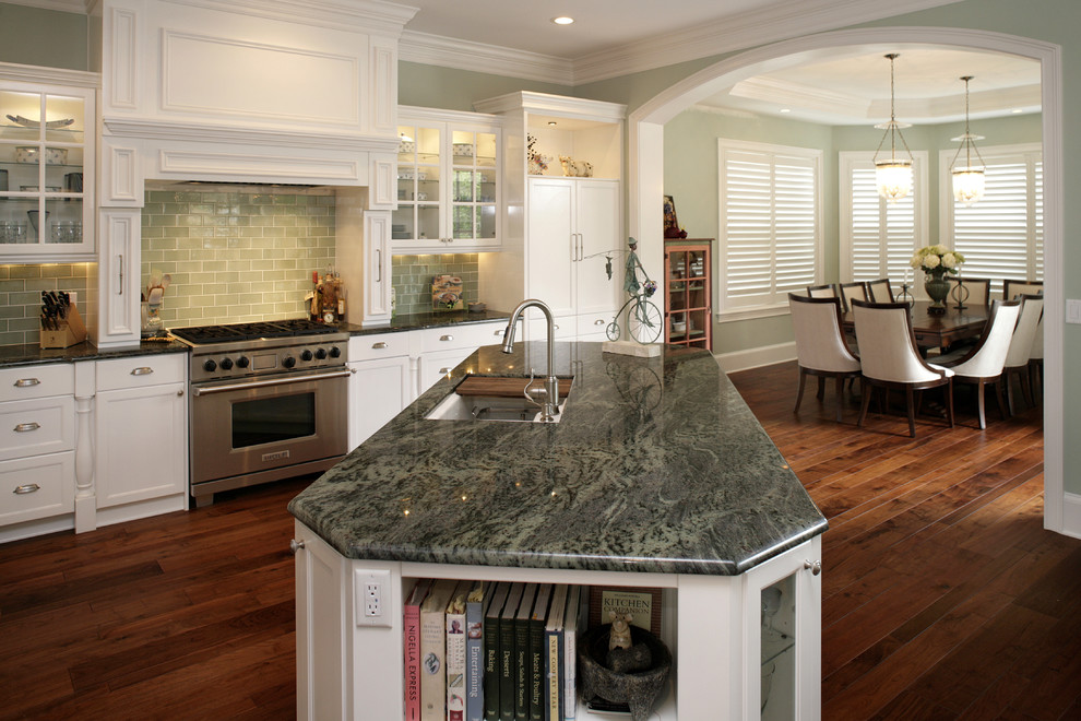Elegant kitchen photo in Tampa with glass-front cabinets, stainless steel appliances, granite countertops, green backsplash and subway tile backsplash