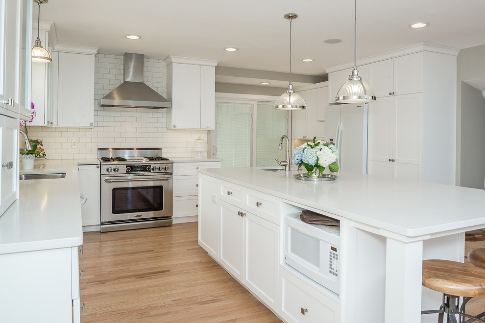 Inspiration for a large timeless l-shaped light wood floor eat-in kitchen remodel in Denver with an undermount sink, shaker cabinets, white cabinets, quartz countertops, white backsplash, ceramic backsplash, stainless steel appliances and an island