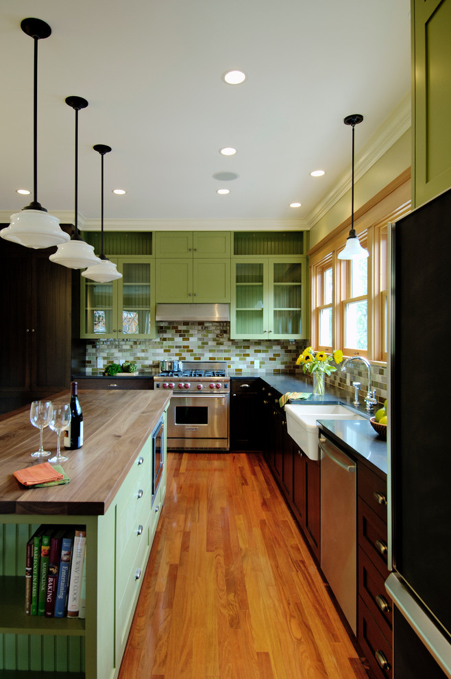 Example of a classic l-shaped kitchen design in Seattle with a farmhouse sink, glass-front cabinets, green cabinets, green backsplash, subway tile backsplash, stainless steel appliances and wood countertops