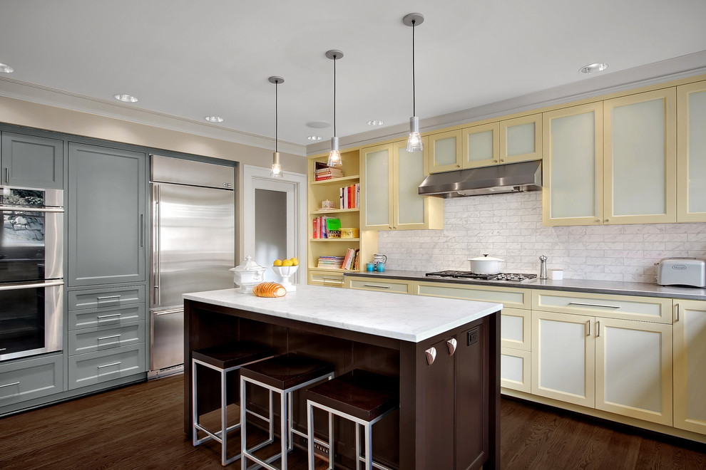 Inspiration for a contemporary kitchen remodel in Seattle with stainless steel appliances, recessed-panel cabinets, yellow cabinets, stainless steel countertops, white backsplash and stone tile backsplash