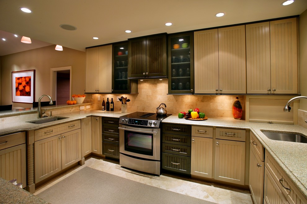 Elegant u-shaped kitchen photo in Miami with an undermount sink, recessed-panel cabinets, beige cabinets, beige backsplash and stainless steel appliances
