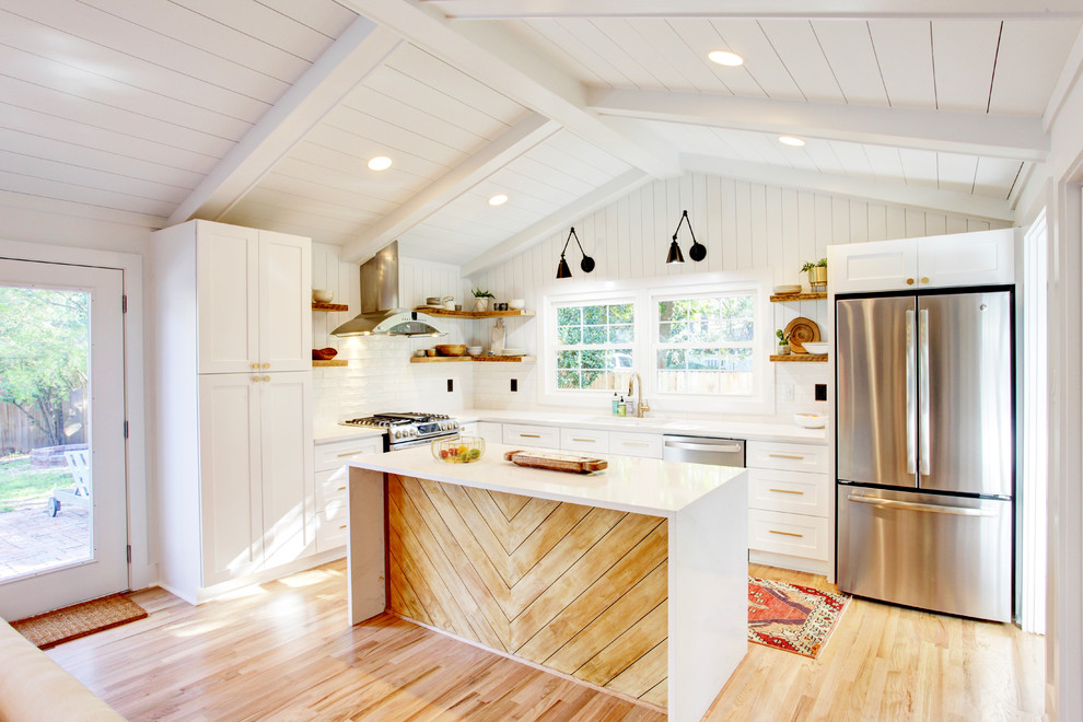 Mid-sized beach style l-shaped light wood floor and beige floor kitchen photo in Atlanta with an undermount sink, white cabinets, quartz countertops, white backsplash, stainless steel appliances, an island, shaker cabinets and white countertops