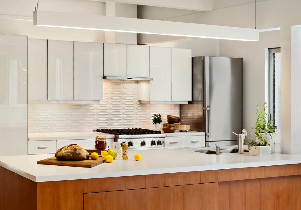 Midcentury modern galley kitchen photo in San Francisco with stainless steel appliances, a double-bowl sink, flat-panel cabinets, white cabinets and white backsplash