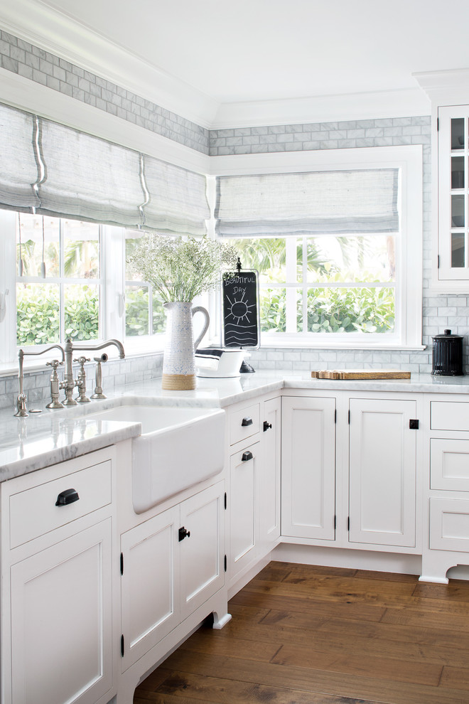 Large beach style l-shaped medium tone wood floor and brown floor open concept kitchen photo in Miami with a farmhouse sink, white cabinets, marble countertops, gray backsplash, marble backsplash, paneled appliances, an island and shaker cabinets