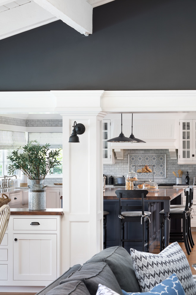 Inspiration for a mid-sized coastal u-shaped medium tone wood floor and brown floor open concept kitchen remodel in Miami with a farmhouse sink, white cabinets, gray backsplash, marble backsplash, paneled appliances, an island, recessed-panel cabinets and wood countertops