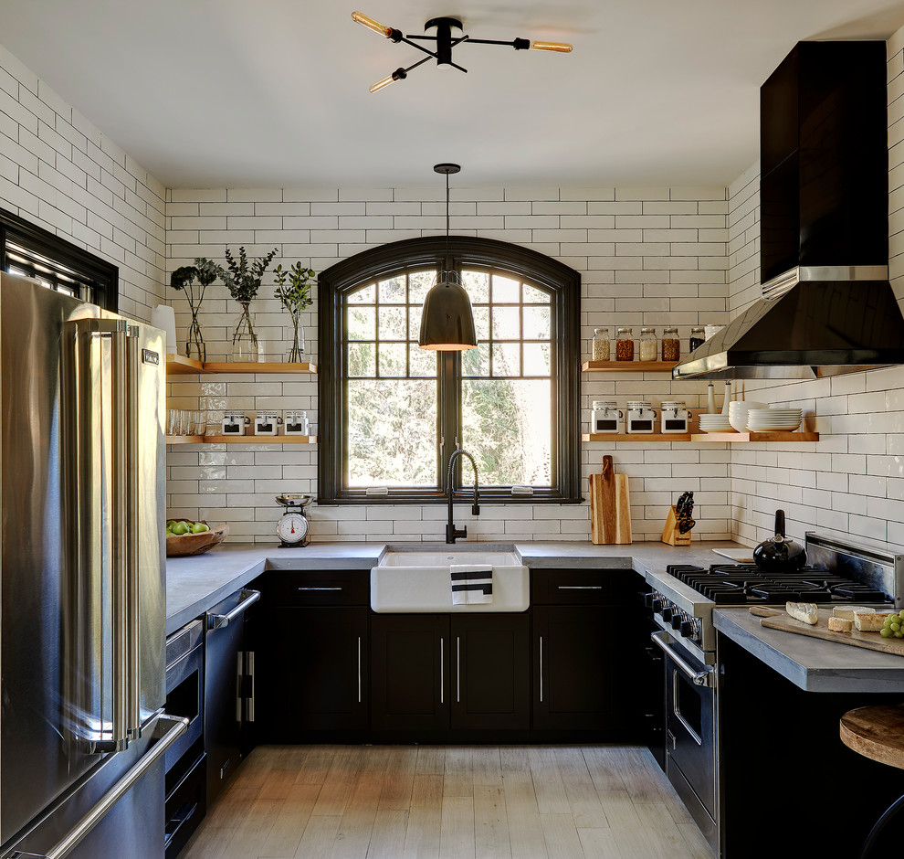Mid-sized farmhouse u-shaped light wood floor and beige floor enclosed kitchen photo in New York with a farmhouse sink, black cabinets, concrete countertops, white backsplash, subway tile backsplash, stainless steel appliances, no island and flat-panel cabinets