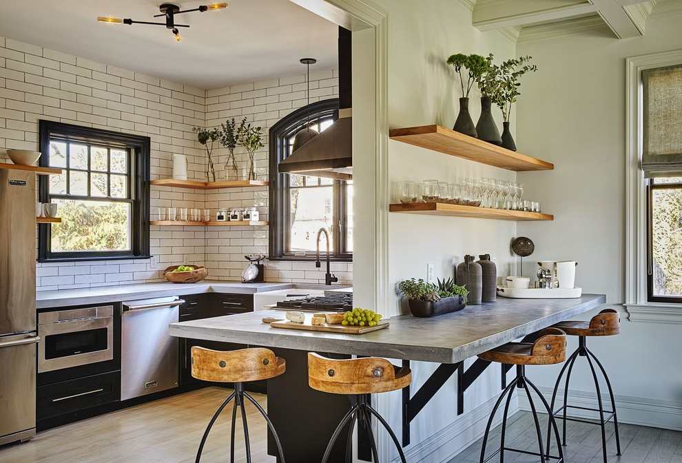 Inspiration for a mid-sized industrial u-shaped light wood floor and beige floor enclosed kitchen remodel in New York with a farmhouse sink, black cabinets, concrete countertops, white backsplash, subway tile backsplash, stainless steel appliances, no island and flat-panel cabinets