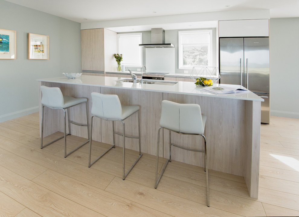 This is an example of a mid-sized scandinavian single-wall eat-in kitchen in Auckland with a double-bowl sink, light wood cabinets, quartz benchtops, white splashback, glass sheet splashback, stainless steel appliances, light hardwood floors and an island.