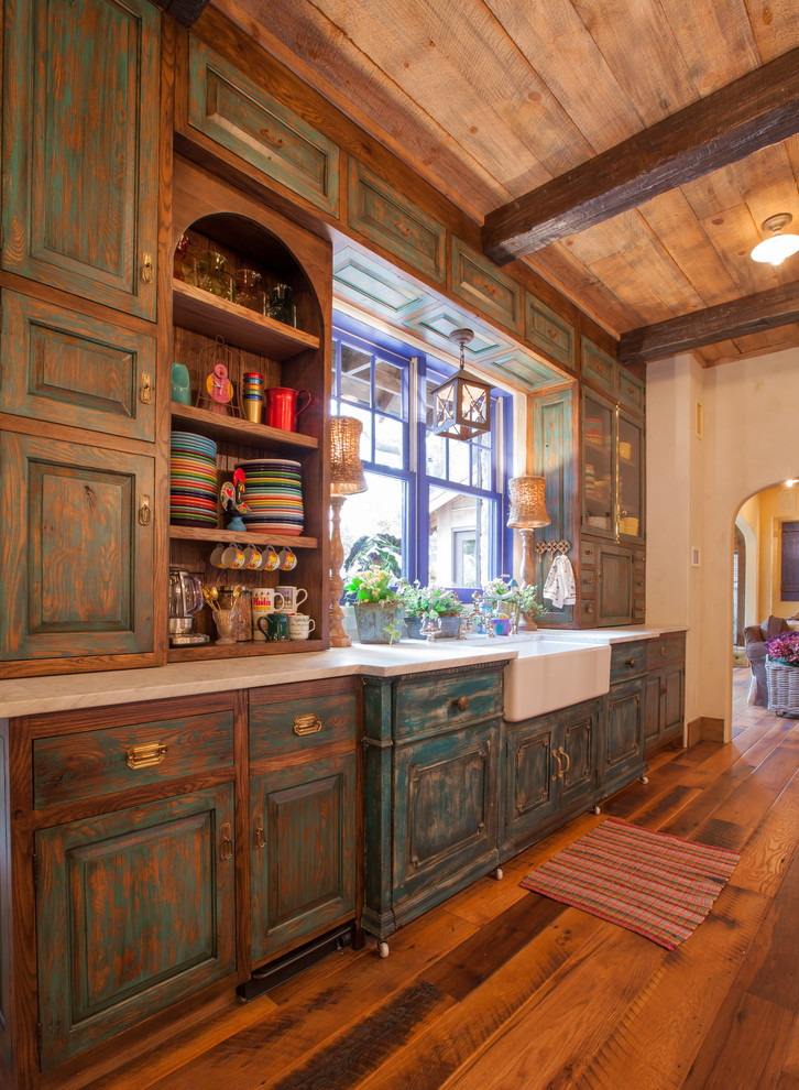 Mountain style galley eat-in kitchen photo in Dallas with a farmhouse sink, distressed cabinets, raised-panel cabinets and soapstone countertops