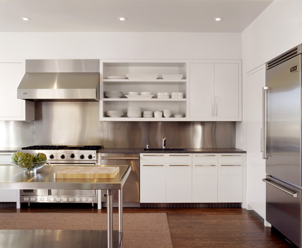 Inspiration for a modern l-shaped kitchen remodel in San Francisco with stainless steel appliances, stainless steel countertops, open cabinets, white cabinets, metallic backsplash and metal backsplash