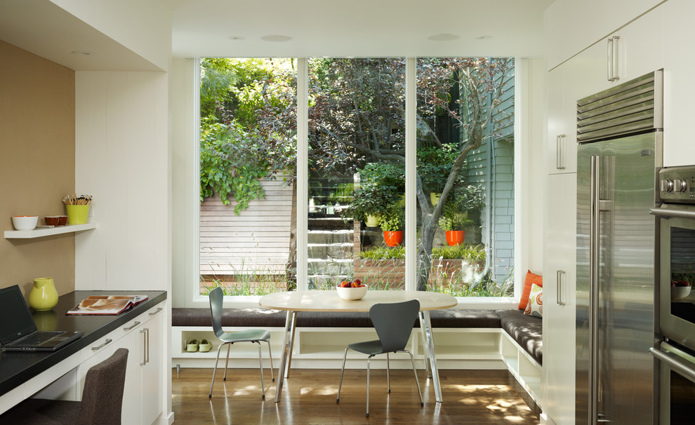 Eat-in kitchen - transitional eat-in kitchen idea in San Francisco with stainless steel appliances, flat-panel cabinets and white cabinets