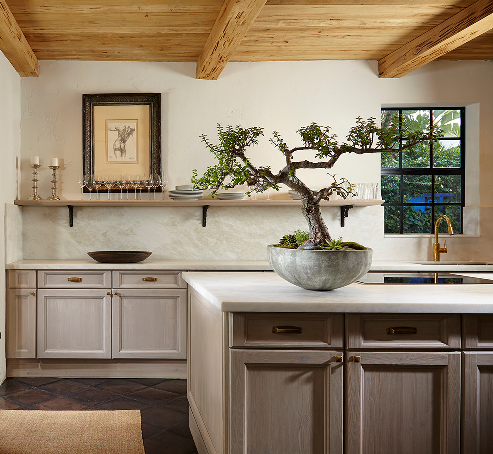 Inspiration for a mediterranean kitchen remodel in Miami with an undermount sink, recessed-panel cabinets, gray cabinets, white backsplash and an island
