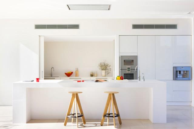 Modelo de cocina comedor de galera, actual, de tamaño medio, con fregadero integrado, armarios con paneles lisos, puertas de armario blancas, encimera de acrílico, salpicadero blanco, electrodomésticos de acero inoxidable, suelo de travertino y una isla