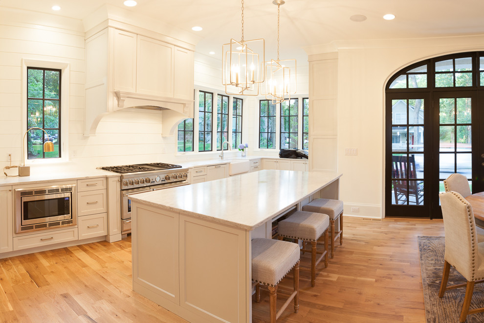 Large transitional l-shaped kitchen photo in Charlotte with white cabinets, marble countertops, stainless steel appliances and an island