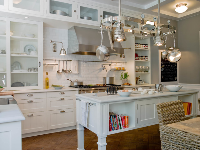Large industrial galley enclosed kitchen in Barcelona with an integrated sink, glass-front cabinets, white cabinets, composite countertops, white splashback, metro tiled splashback, stainless steel appliances, medium hardwood flooring and an island.