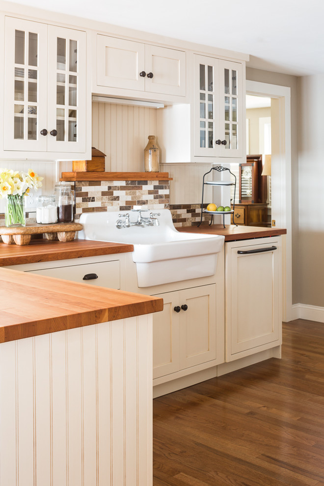 Inspiration for a coastal medium tone wood floor kitchen remodel in Portland Maine with a farmhouse sink, shaker cabinets, white cabinets, wood countertops, brown backsplash and a peninsula