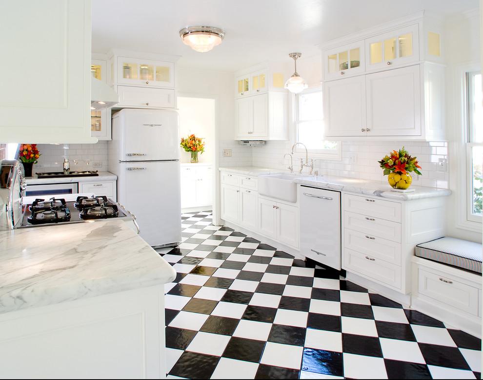 Elegant u-shaped multicolored floor enclosed kitchen photo in San Francisco with a farmhouse sink, marble countertops, white appliances, white cabinets, white backsplash and subway tile backsplash