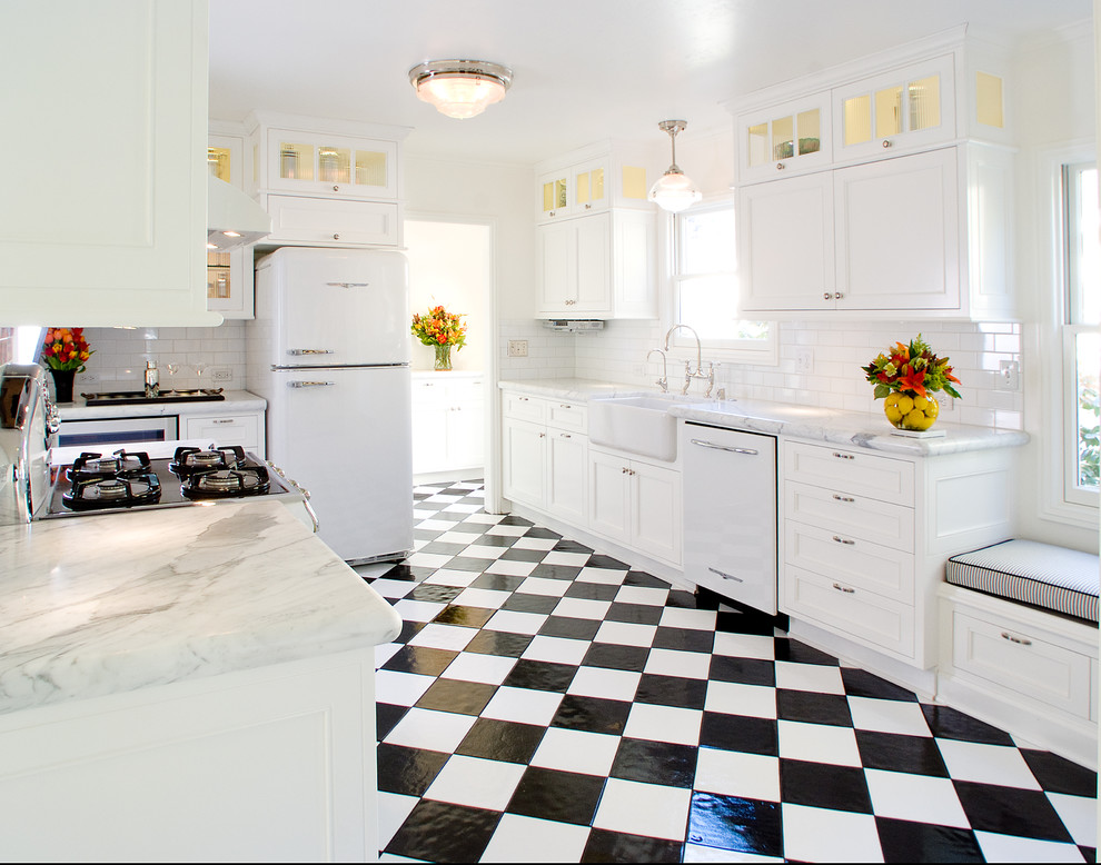 Elegant u-shaped multicolored floor enclosed kitchen photo in San Francisco with a farmhouse sink, marble countertops, white appliances, white cabinets, white backsplash and subway tile backsplash