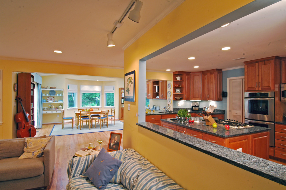 Example of a classic open concept kitchen design in DC Metro with stainless steel appliances, granite countertops, raised-panel cabinets and medium tone wood cabinets