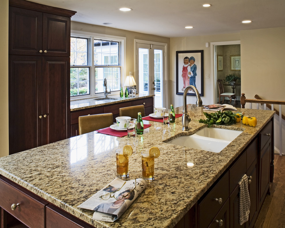 Example of a classic kitchen design in DC Metro with a double-bowl sink, granite countertops, raised-panel cabinets and dark wood cabinets