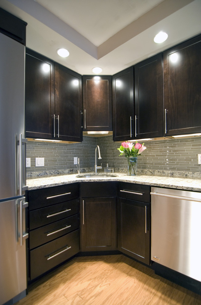 Example of a trendy kitchen design in DC Metro with stainless steel appliances, granite countertops, an undermount sink, recessed-panel cabinets, dark wood cabinets and green backsplash