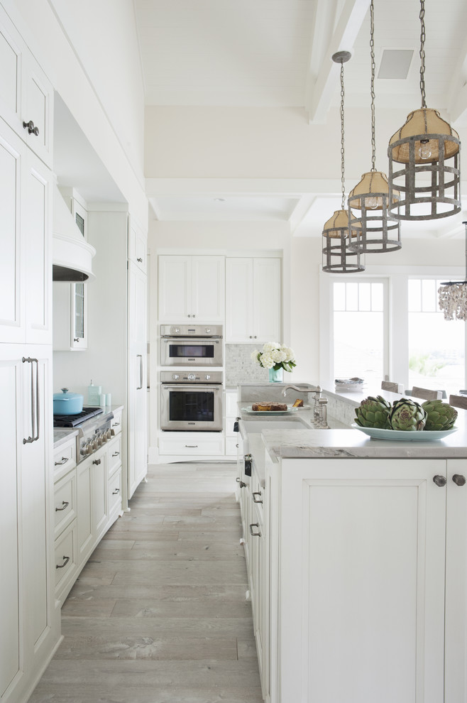 Example of a large beach style l-shaped light wood floor and beige floor open concept kitchen design in Atlanta with a farmhouse sink, recessed-panel cabinets, white cabinets, marble countertops, multicolored backsplash, mosaic tile backsplash, stainless steel appliances and an island
