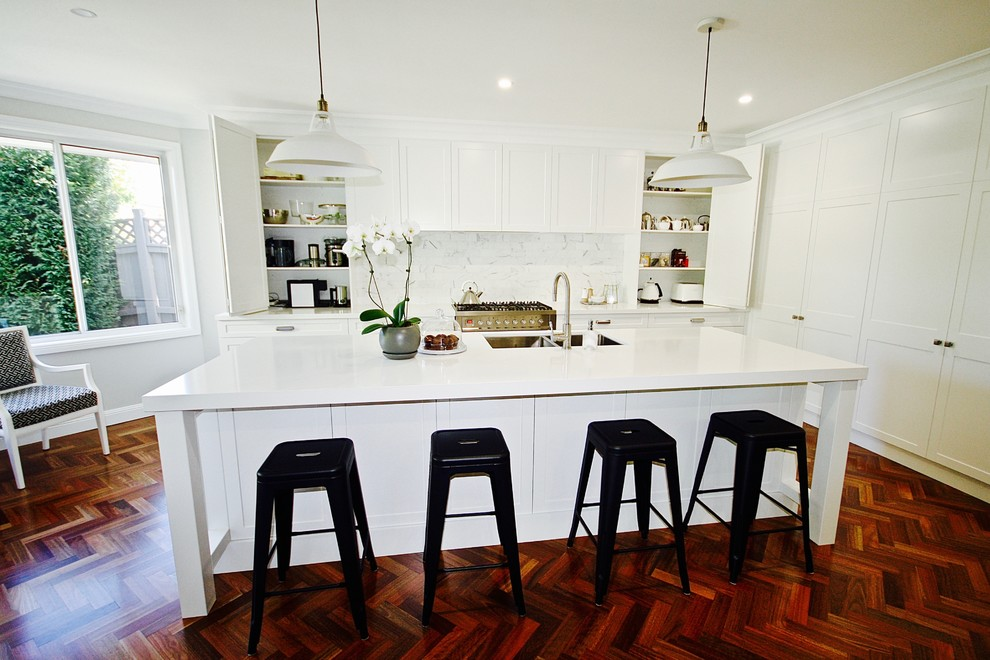 Inspiration for a large transitional l-shaped open plan kitchen in Sydney with an undermount sink, shaker cabinets, white cabinets, quartz benchtops, white splashback, stone tile splashback, stainless steel appliances, dark hardwood floors and an island.