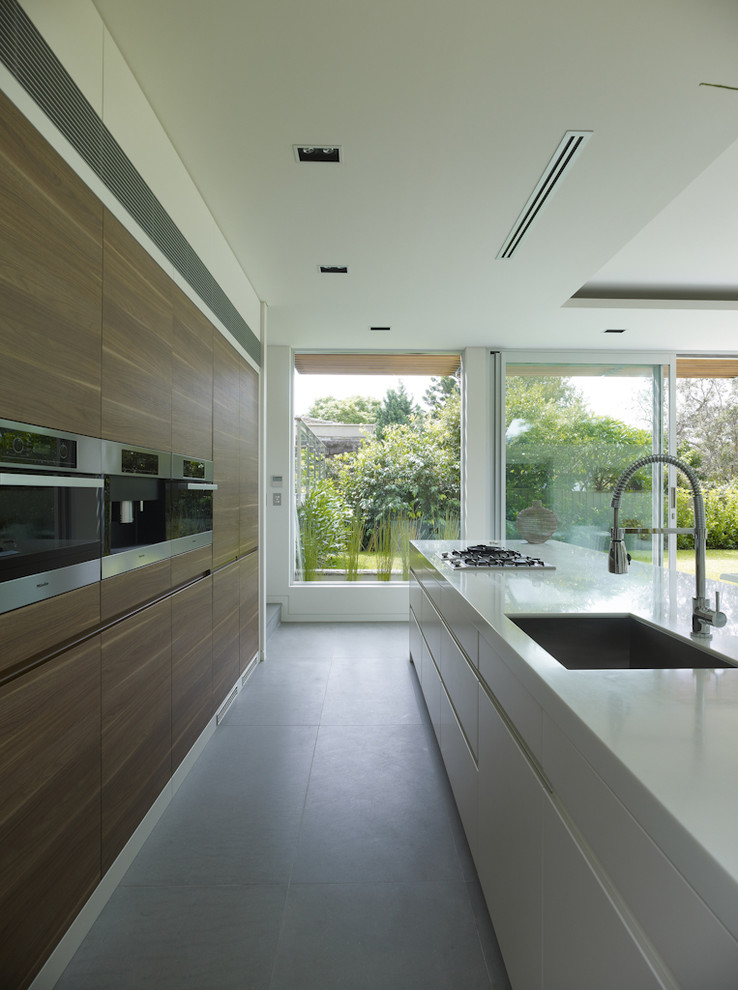 Inspiration for a mid-sized contemporary galley slate floor eat-in kitchen remodel in Sydney with an undermount sink, flat-panel cabinets, quartz countertops, stainless steel appliances and an island