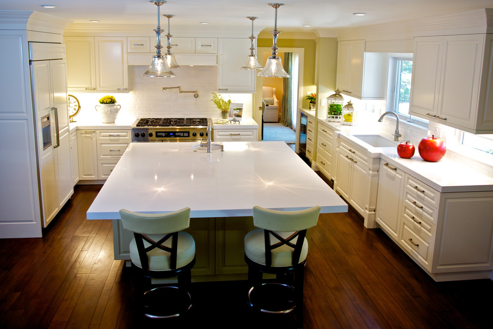 Open concept kitchen - large traditional u-shaped medium tone wood floor open concept kitchen idea in Los Angeles with white cabinets, white backsplash, subway tile backsplash, paneled appliances, an undermount sink, raised-panel cabinets, quartz countertops and an island